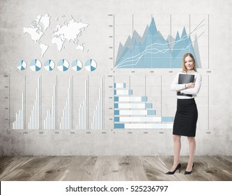 Portrait of blond businesswoman hugging her folder and standing near a concrete wall with graphs and world map. Elements of this image furnished by NASA