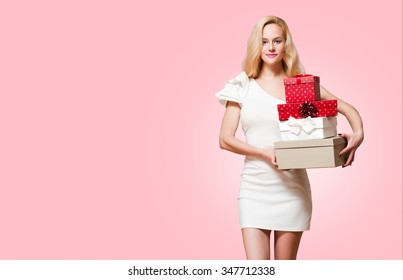 Portrait of a blond Christmas beauty holding gift boxes.