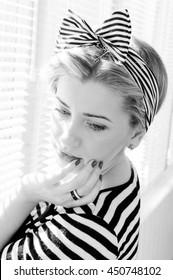 Portrait of blond elegant girl on sunny windows background