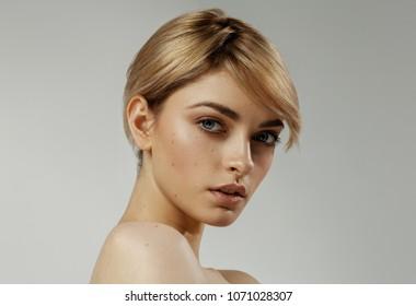 Portrait of blond female model isolated on grey background