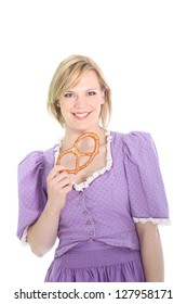 Portrait of a blond german girl, wearing a lavender dirndl dress and holding a bretzel. On white