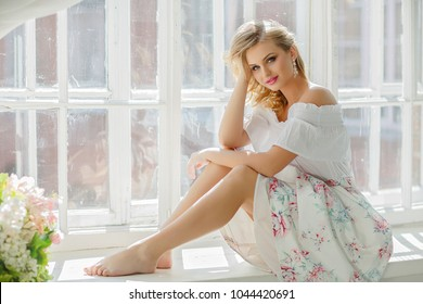 Portrait of a blond girl with blue eyes in a summer dress sitting on a window. Summer sunny day