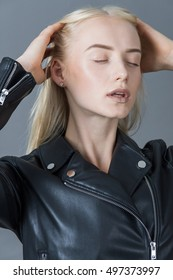Portrait of a blond girl in a leather jacket gray studio background
