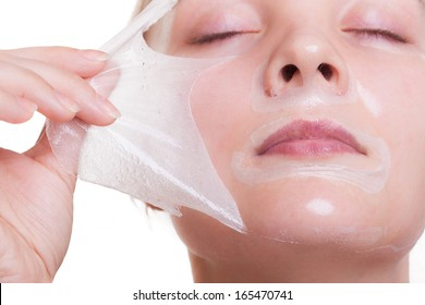 Portrait of blond girl young woman in facial peel off mask. Peeling. Beauty and body skin care. Isolated on white background. Studio shot.