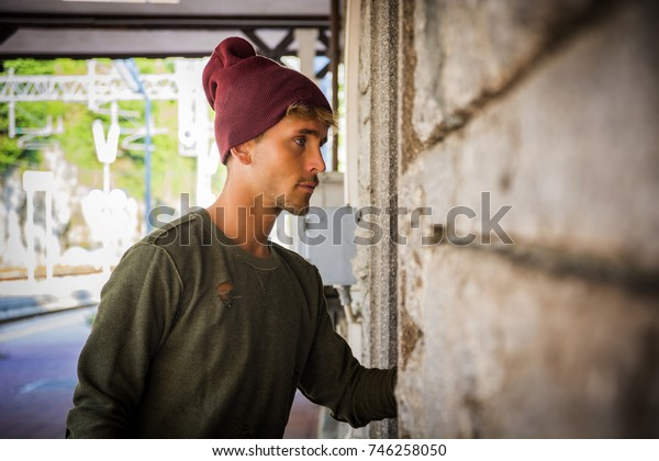 Portrait of blond haired handsome young man with wool hat. An old train station is behind him in Italian town