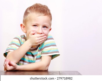 Portrait of blond happy laughing boy child kid covering mouth with his hand at the table interior. Emotions and fun.