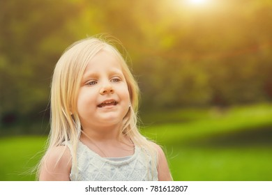 Portrait of blond little Caucasian girl wearing white dress walking and smiling in summer day