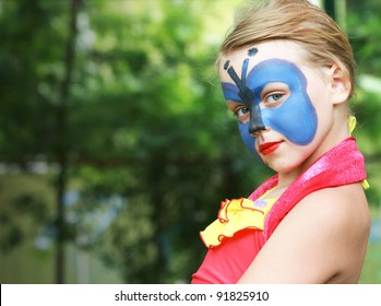 Portrait of a blond little girl with painted blue Butterfly mask on the face