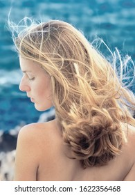 Portrait of a blond, long-haired woman in back view with left side profile. She is white-skinned and has bare shoulders and back, in the background the blue of the Atlantic Ocean.