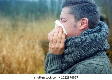 portrait of blond man outdoors blowing his nose