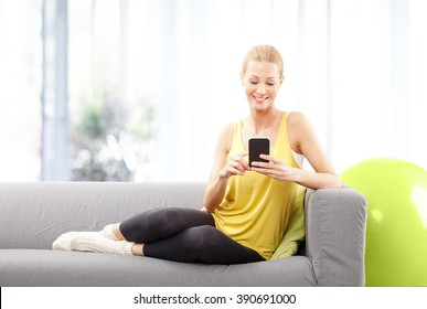 Portrait of blond mature woman using her mobile phone while sitting at home after fitness workout.