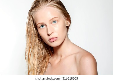Portrait of a blond model with wet hair and clean skin after shower isolated on white background