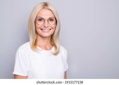 Portrait of blond optimistic old lady near empty space wear spectacles white cloth isolated on grey color background