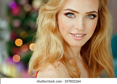 Portrait of blond, sensual , blue-eyed girl with freckles in a white fur Cape on the Christmas tree, close-up