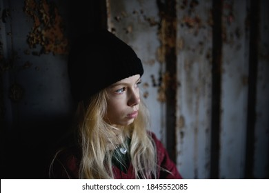 Portrait of blond teenager girl standing indoors in abandoned building.