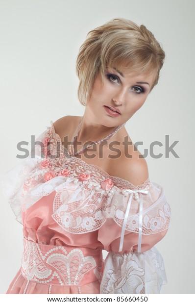 Portrait of blond woman in beautiful long pink dress