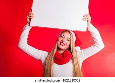 portrait of a blond woman in christmas mood with jelly bag santa hat scarf and sweater isolated against red backdrop holding white board above her head smiling into the camera.