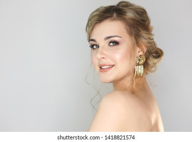 Portrait of the blond woman with fashion hairstyle and makeup wearing big golden earrings
