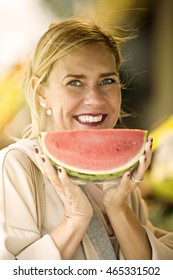portrait of blond woman holding a melon and smiles