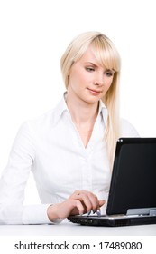 Portrait of blond woman sitting by laptop and working