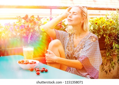 portrait of a blond woman sitting on balcony and enjoying the sun
