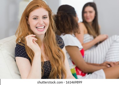 Portrait of a blond with young female friends chatting on sofa in background