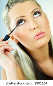 Portrait of blond young sexy woman doing makeup