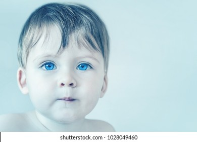 Portrait of a blonde baby boy with big blue eyes. Toned