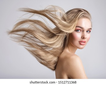 Portrait of a blonde beautiful woman with a long straight light hair. Woman with hair flying in the wind.  Portrait of a beautiful woman with a coral color makeup. Fashion model. Flying hair.