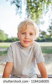 Portrait of blonde boy sitting on bench after school classes.