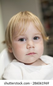 portrait of blonde caucasian baby nineteen month age chubby face looking at camera with serious expression