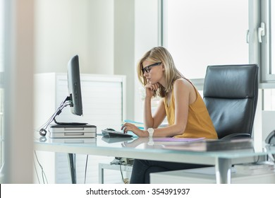 Portrait of a blonde female business partner in her 30's sitting at her tidy glass desk and typing on the keyboard of her computer in a luminous white office. She is wearing a yellow top and glasses.