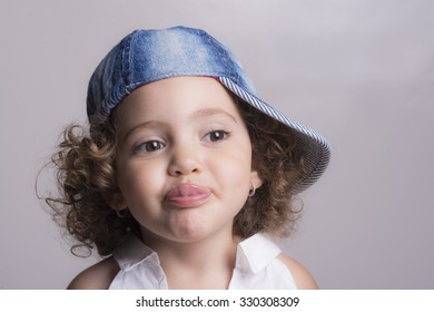 Portrait of a blonde female child smiling with the tongue out and a jeans hat
