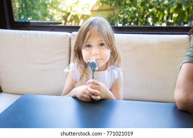 portrait of blonde four years old girl sitting in a restaurant, with spoon in her hands looking at