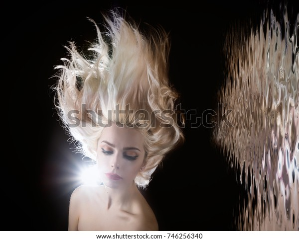 Portrait of a blonde girl with beautiful hair. Reflected in water surface.