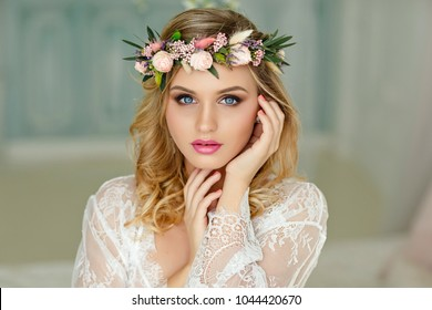 Portrait of a blonde girl with blue eyes with a wreath of flowers on her head. Close-up, Beauty