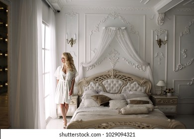 portrait of a blonde girl, bride, sits on the royal bed. Natural light