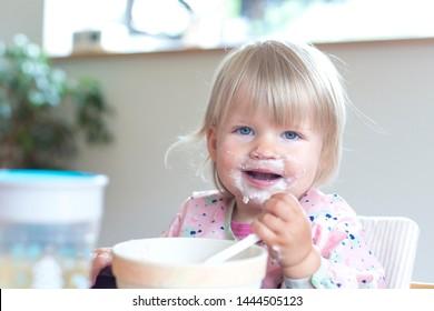 Portrait of blonde girl eating in highchair