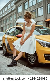 Portrait of blonde girl with flyaway hair in the background of New York City street with taxi cabs. Elegant businesswoman walking on city street