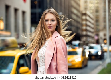 Portrait of blonde girl with flyaway hair in the background of New York City street with taxi cabs. Elegant businesswoman walking on city street.