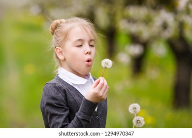 Portrait of a blonde girl in gray jacket standing against background of flowering trees. Kid with white dandellion.