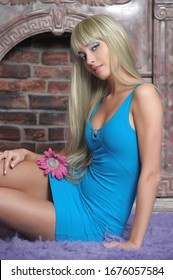 portrait of a blonde girl with long hair in a blue dress sitting