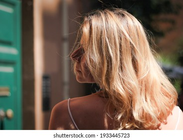 Portrait of a blonde, a girl in profile with beautiful long hair, surrounded by an urban background