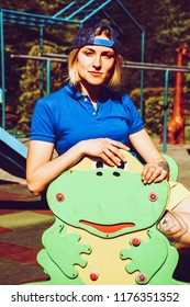 Portrait of a blonde girl with a short haircut. Background  sports ground. Dark blue t-shirt polo and yellow shorts.Sport shooting.