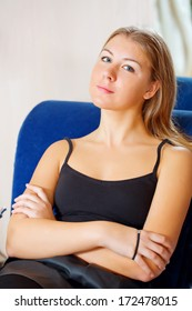 Portrait of blonde girl sitting on sofa and resting