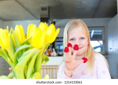 Portrait of blonde girl smiling with red raspberries on her fingers