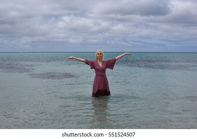 portrait of a blonde girl wearing a long purple dress standing in he ocean and touching the water