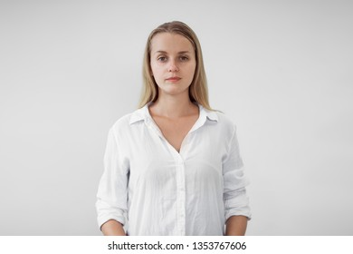Portrait of blonde girl in white shirt on white background, looking at camera