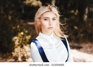 Portrait of blonde girl in white shirt in the park