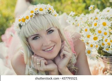 A portrait of blonde girl with a wreath of daisies on her head. Blond girl with curly hair in chamomile field with a large bouquet of daisies